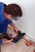 Plumber drilling a wall — Stock Photo