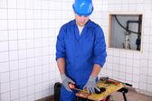 Junior plumber taking measurements — Stock Photo