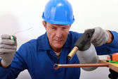 Craftsman soldering a copper pipe — Stock Photo