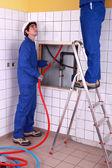 Two plumber fixing bathroom water supply — Stock Photo