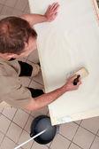 Handyman applying glue on wallpaper — Stock Photo