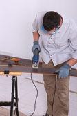 Man met een elektrische puzzel te snijden een stuk van houten vloeren — Stockfoto