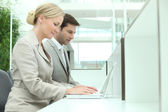 Man and woman working on computers — Stock Photo