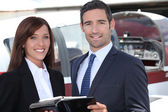 Couple standing by the cockpit of a light aircraft — Stock Photo