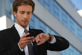 City businessman checking his watch and his phone — Stock Photo