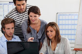 Young gathered round a laptop — Stock Photo