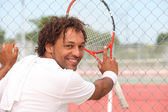 Male tennis player leaning on the fence of a municipal hard court — Stock Photo