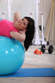 Young woman doing stability ball abs exercises in the gym — Stok fotoğraf