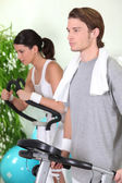 Young couple using gym equipment — Stock Photo