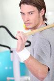 Hombre usando un palo en un gimnasio — Foto de Stock
