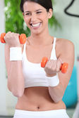 Woman laughing while lifting dumbbells — Stock Photo