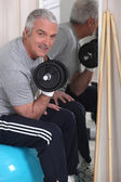 Grey-haired man lifting weights — Stock Photo