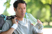 Man in sports clothes drinking water — Stock Photo