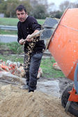Labourer shovelling gravel into a mixer — Stock Photo