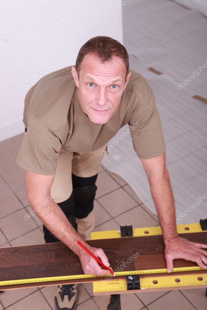 Man at home cutting wooden flooring to size — Stock Photo #7811301