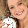 Blonde Woman holding alarm clock — Stock Photo