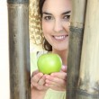 Woman holding apple stood by bamboo — Stock Photo