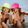Two female friends at the beach giving thumbs-up — Stock Photo #7886259