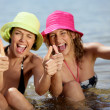 Stock Photo: Two female friends at the beach giving thumbs-up