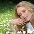 Stock Photo: Womlying in daisies