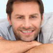 Closeup of a smiling man with stubble resting his head on his arms — Stock Photo #7886809