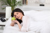 Brunette laying on bed holding apple — Stock Photo