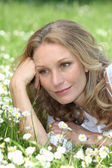 Woman lying in the daisies — Stock Photo