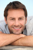 Closeup of a smiling man with stubble resting his head on his arms — Stock Photo