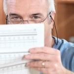 homme dans des verres de lecture d'une feuille imprimée — Photo