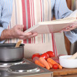 A man reading a recipe book in his kitchen — Stock Photo #7891299