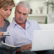 A mature couple purchasing on internet — Stock Photo