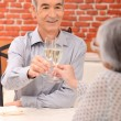 Senior couple drinking champagne in a restaurant - Stock Photo