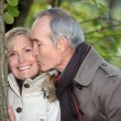 Older man kissing his partner under a tree — Foto de Stock