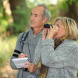 Couple of retirees observing wildlife with binoculars in forest — Stock Photo