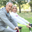Elderly couple on bike ride - Stock Photo