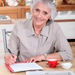 A senior woman writing a letter — Stock Photo