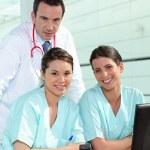 Physician and female nurses — Stock Photo