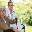Elderly woman and young female caregiver at home - Stock Photo