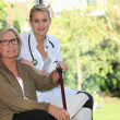 Foto Stock: Elderly womand young female caregiver at home