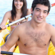 Young couple in inflatable dingy - Stock Photo