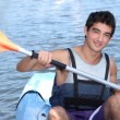 Stock Photo: Young msmiling in canoe