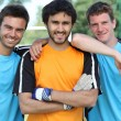 Royalty-Free Stock Photo: Three smiling footballers with ball