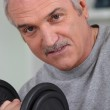 Senior man doing exercises with a dumbbell — Stock Photo