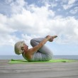 Senior woman making exercises on the beach — Stock Photo #7897068