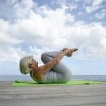 年配の女性、ビーチでの演習を行う — ストック写真