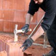 Stock Photo: Builder hammering brick