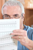 Man in glasses reading a printed sheet — Stock Photo