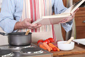 A man reading a recipe book in his kitchen — Stock Photo