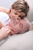 Senior couple laid in a bed — Stock Photo