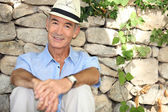 Senior man sitting in the shade of a stone wall — Stock Photo